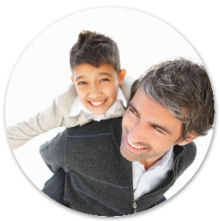 Mature man piggybacking his excited son over white background with copyspace